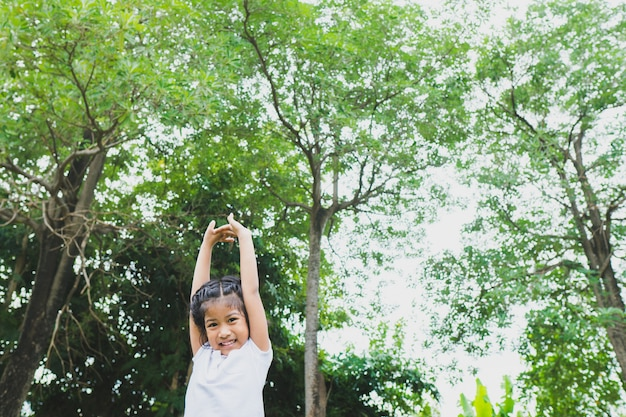 Petite fille asiatique faisant du yoga dans le parc public. Photo Premium