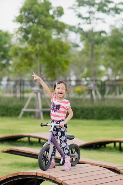 Petite fille asiatique heureuse faire du vélo au terrain de jeux Photo Premium