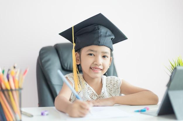 Petite fille asiatique portant chapeau diplômé à faire ses devoirs et sourire avec bonheur Photo Premium