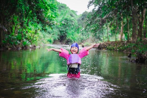 Petite Fille Asiatique Portant Des Manches Gonflables Jouant Dans L'eau De La Nature En Vacances Photo Premium