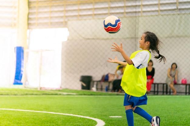 Petite fille asiatique s'entraîne sur un terrain de football en salle Photo Premium