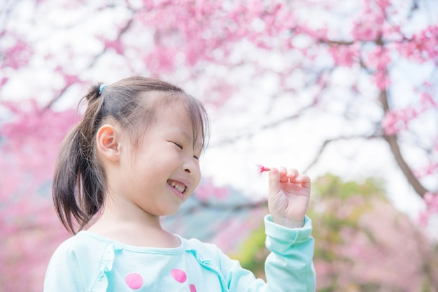 Petite fille asiatique souriante devant l'arbre de sakura. Photo Premium