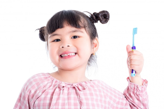 Petite Fille Asiatique Tenant La Brosse à Dents Et Sourires Sur Fond Blanc Photo Premium