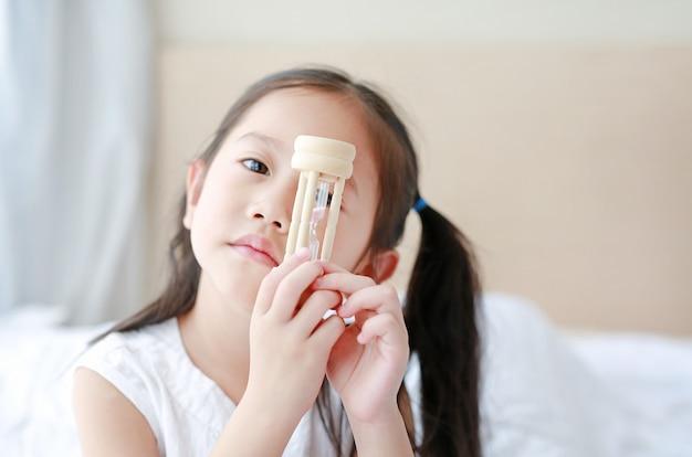 Petite fille asiatique tenant un sablier dans la main avec regardant à travers la caméra Photo Premium