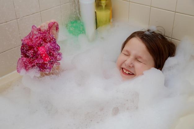 Une petite fille assise dans la baignoire jusqu'au cou, en s'amusant, souffle des bulles Photo Premium