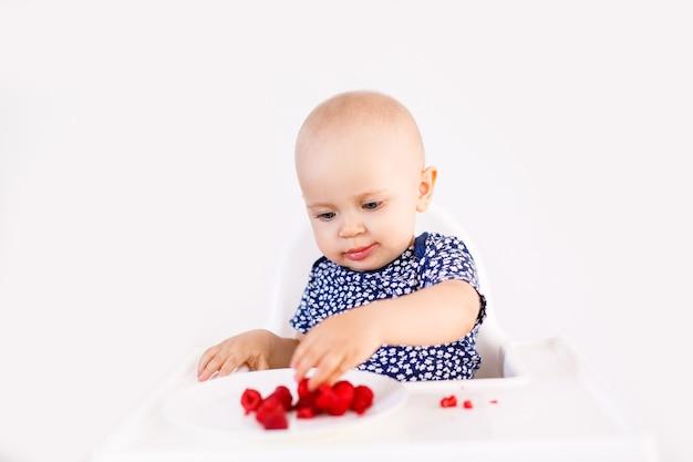 Petite Fille Assise Dans Une Chaise Haute Pour Enfant Manger Des Baies Sur Blanc Photo Premium