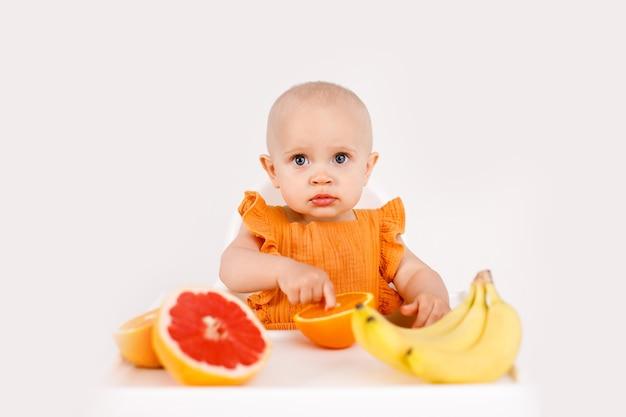 Petite Fille Assise Dans Une Chaise Haute Pour Enfant, Manger Des Fruits Sur Blanc Photo Premium