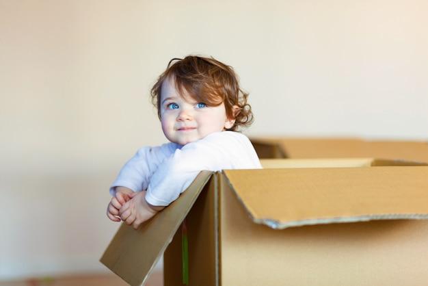Petite fille assise à l'intérieur d'une boîte en carton brune. Photo Premium