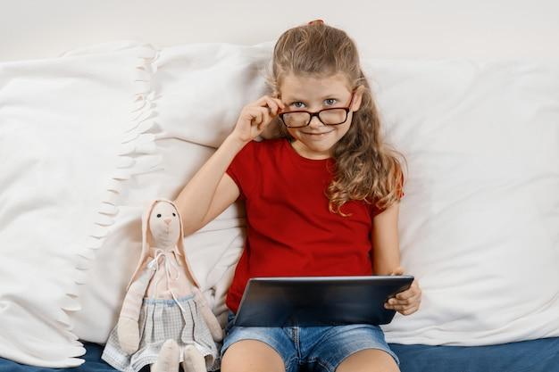 Petite Fille Assise à La Maison Dans Son Lit Avec Jouet Et Tablette Numérique Photo Premium