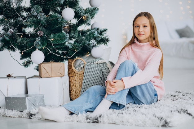 Petite Fille Assise Par Arbre De Noël Photo gratuit