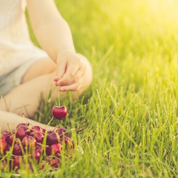 Une petite fille assise sur une pelouse verte prend une baie mûre dans une assiette de cerises douces Photo Premium