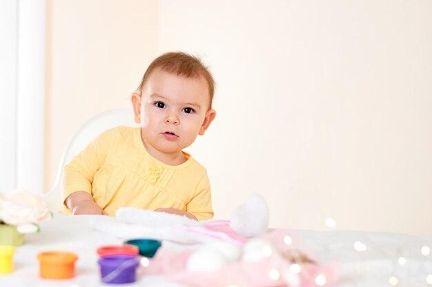 Petite fille assise à la table et la peinture des oeufs de pâques de vacances souriant heureuse enfance Photo Premium
