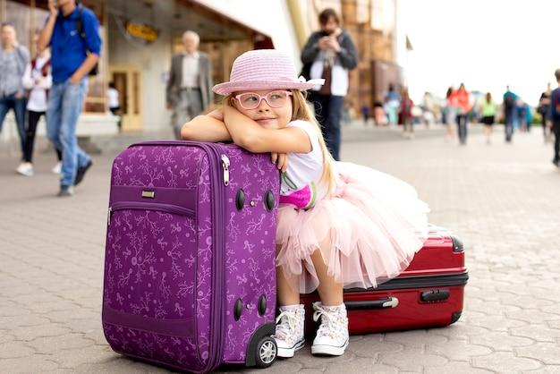 Petite fille assise sur une valise à la gare. Photo Premium