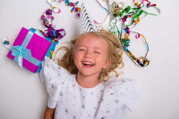 Petite Fille Au Chapeau D'anniversaire Souriant Avec Boîte-cadeau Et Confettis Photo Premium