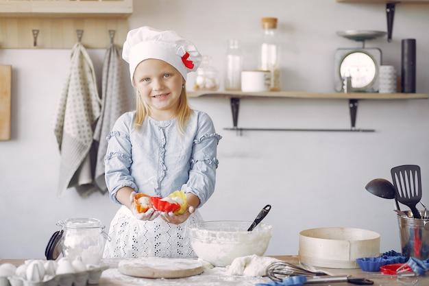 Petite fille au chapeau blanc de shef cuire la pâte pour les biscuits Photo gratuit