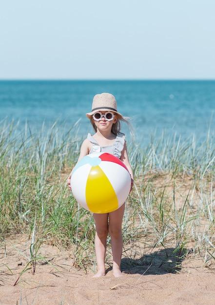 Petite Fille Au Chapeau Jouant Sur La Plage Avec Ballon, Journée D'été Ensoleillée. Concept De Vacances Photo Premium