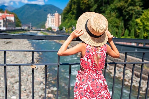 Petite fille au chapeau sur le quai d'une rivière de montagne dans une ville européenne, Photo Premium