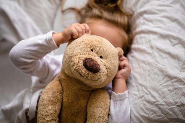 Petite Fille Au Lit Avec Peluche Les émotions D'un Enfant, Lit Blanc Photo gratuit