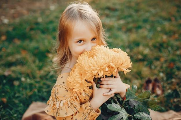 Petite fille en automne parc Photo gratuit