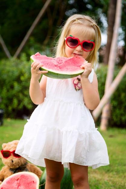 Petite fille aux cheveux blonds dans des lunettes de soleil en train de manger de la pastèque sur le parc, prochain ours en peluche Photo Premium