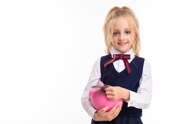 Une Petite Fille Aux Cheveux Blonds En Peluche Avec Une Queue De Cheval, De Grands Yeux Bleus Et Un Joli Visage Plie Des Dollars Dans Une Tirelire. Photo Premium