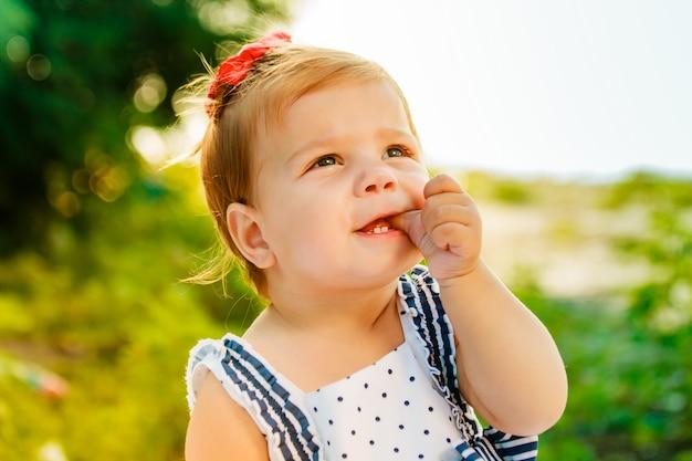 La petite fille aux cheveux courts suce le doigt. le bébé regarde dans le ciel. petit bel enfant assis sur la rive de la rivière parmi les arbres verts. Photo Premium