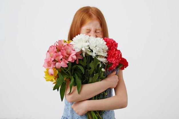 Petite Fille Aux Cheveux Roux De Taches De Rousseur, Fermée Et A L'air Mignonne, Tient Le Bouquet Et Apprécie L'odeur Des Fleurs, Porte Un T-shirt Jaune, Se Tient Sur Fond Rose. Photo gratuit