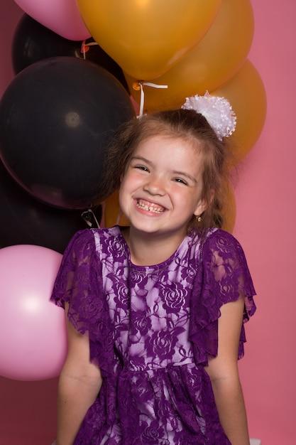 Petite fille aux cheveux sombre avec des ballons colorés sur fond rose Photo Premium