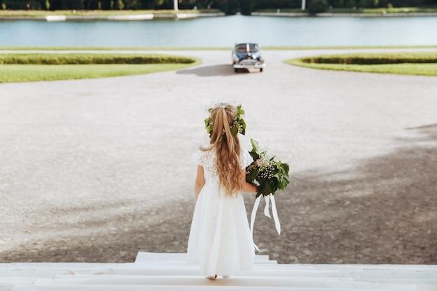 Petite fille aux fleurs regarde la voiture rétro noire qui monte vers la maison Photo gratuit