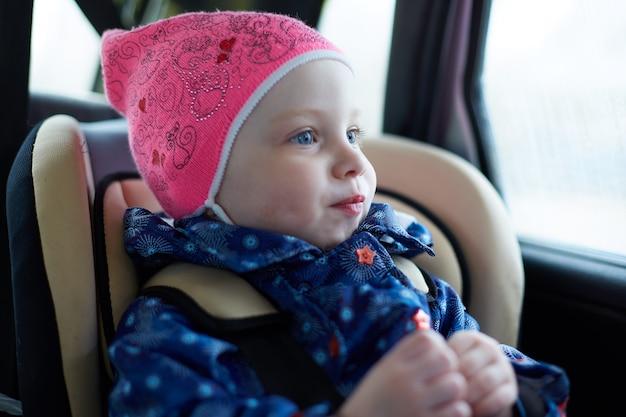 Petite Fille Aux Yeux Bleus Assis Dans Un Siège Enfant Sur Le Siège Arrière De La Voiture à La Fenêtre Photo Premium