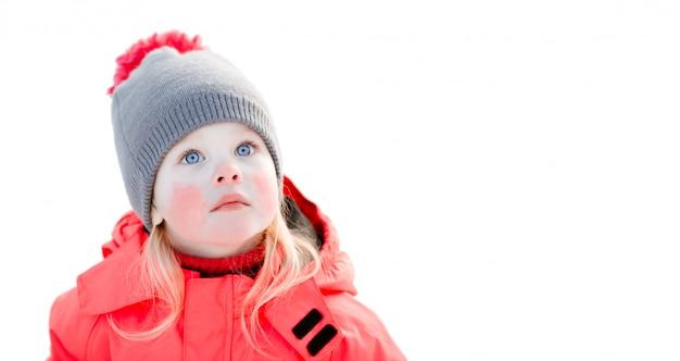 Une petite fille aux yeux bleus avec un bonnet tricoté et une veste d'hiver rose lève les yeux. gros plan, isolé, blanc Photo Premium
