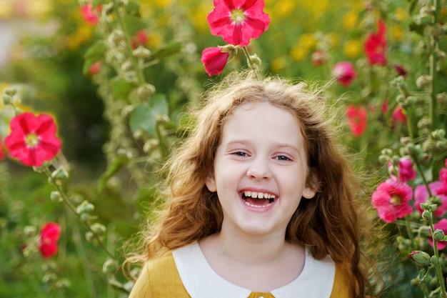 Petite fille ayant des yeux heureux et montrant des dents blanches. Photo Premium