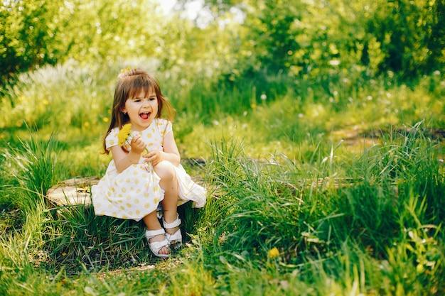 Une petite fille avec de beaux cheveux longs et dans une robe jaune joue dans le parc de l'été Photo gratuit