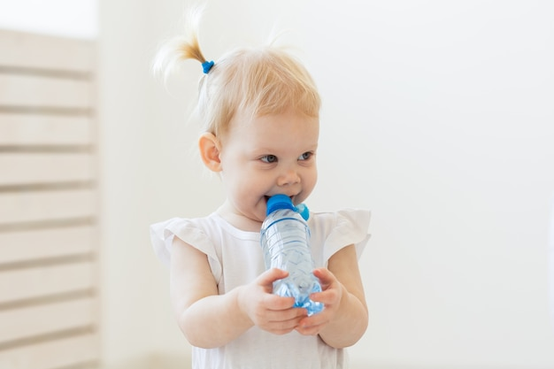 Petite Fille De Bébé Tout-petit Avec Une Bouteille D'eau à La Maison Photo Premium