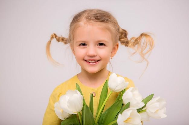 Petite fille blonde avec un bouquet de tulipes sur fond clair Photo Premium
