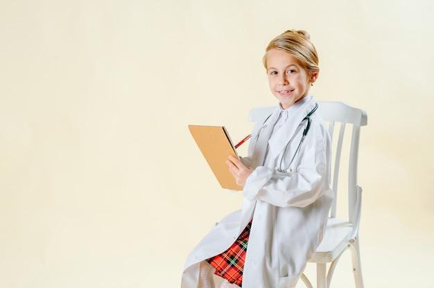 Petite fille blonde en costume de médecin fait une entrée dans un cahier Photo Premium
