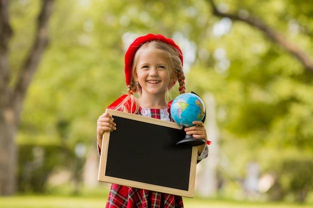 Petite fille blonde première niveleuse en robe rouge et béret tenant un dessin vide et globe Photo Premium