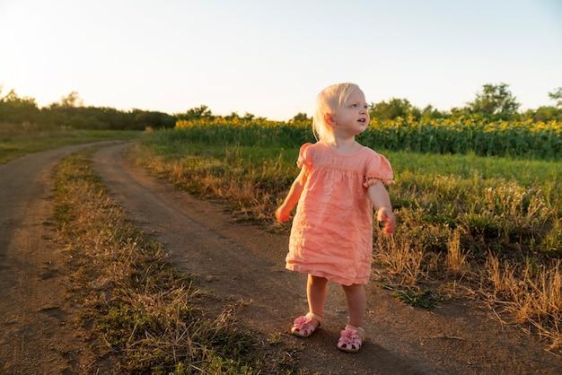 Petite Fille Blonde En Robe Rose Se Promene Le Long De La Route De Campagne Photo Premium