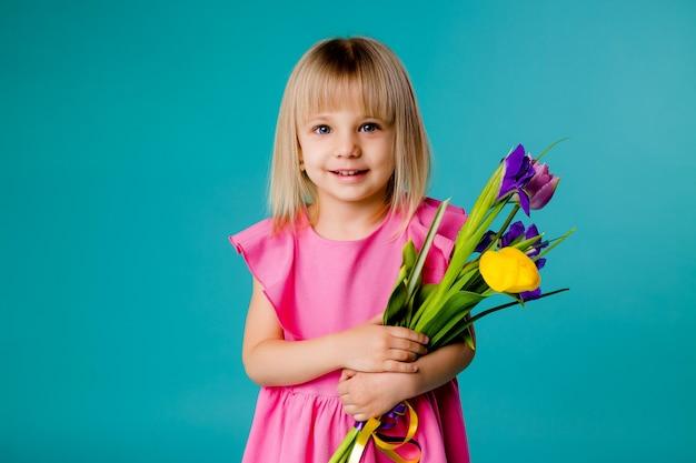 Petite Fille Blonde Sourit Dans Une Robe Rose Et Tenant Un Bouquet De Fleurs De Printemps Sur Un Espace Bleu Isoler Photo Premium