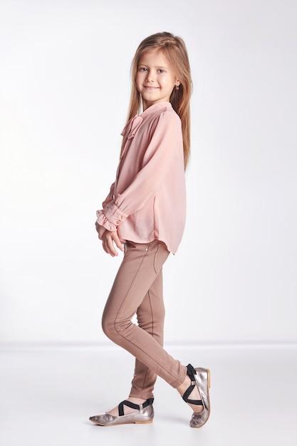 Petite fille en blouse rose et pantalon posant Photo Premium