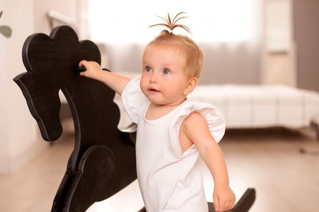 Petite Fille En Bonne Santé Dans Une Pièce à Côté D'un Canapé Gris Apprend à Marcher Photo Premium