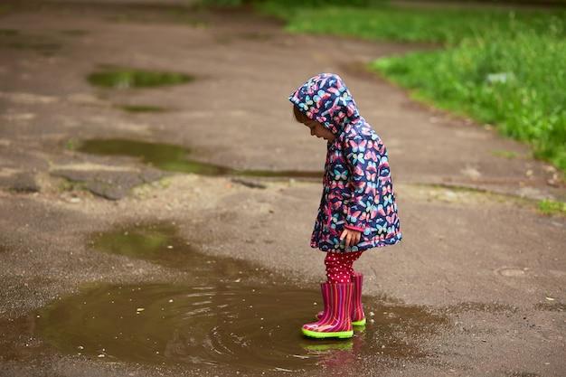 Petite fille en bottes en caoutchouc s'amuse à marcher dans les piscines après la pluie Photo gratuit