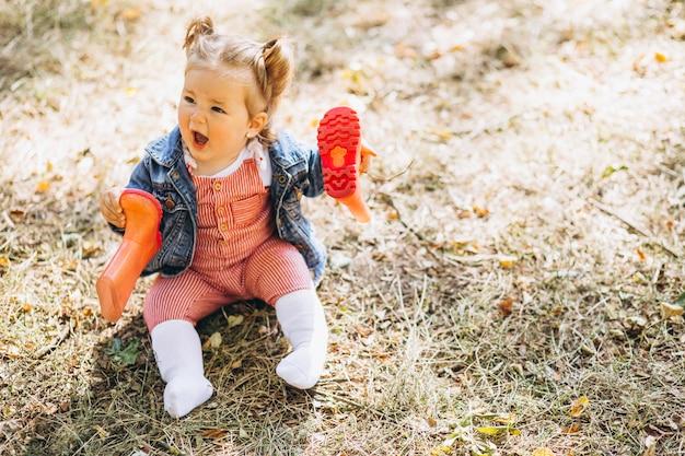 Petite fille avec des bottes de pluie assis dans un parc Photo gratuit