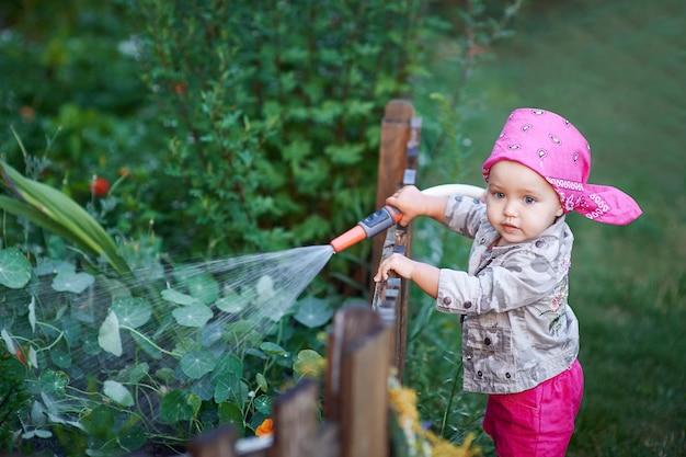 Petite fille en bottes roses arrosant les fleurs Photo Premium