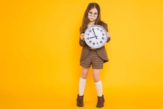 Petite fille brune en costume avec des horloges Photo Premium