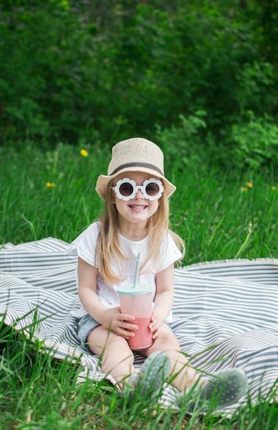 Petite Fille Buvant Un Délicieux Smoothie Aux Fraises Avec Du Lait Et De La Crème Glacée, En Plein Air, Le Concept D'été, Des Aliments Sains Photo Premium