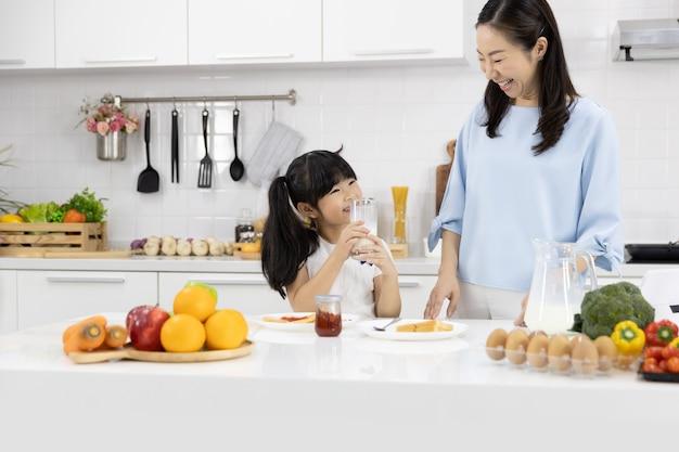 Petite fille buvant du lait dans la cuisine à la maison Photo Premium