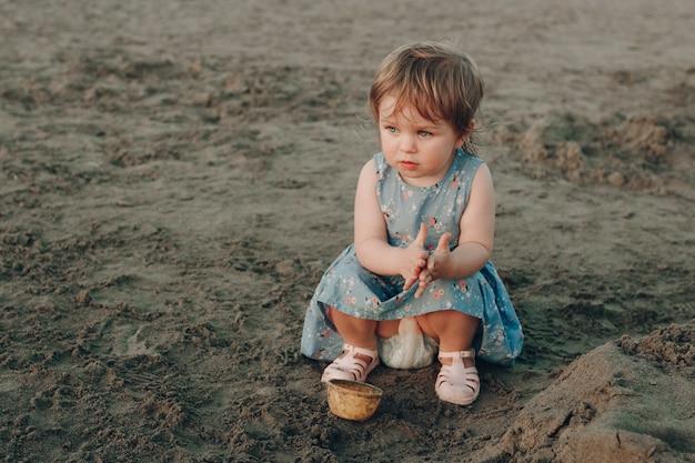 Petite fille caucasienne s'amuser à creuser dans le sable à la plage de l'océan, construction d'un château de sable Photo gratuit