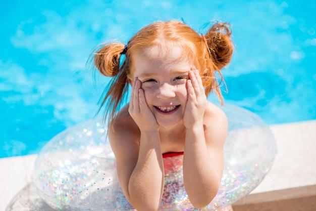 Petite fille avec un cercle de natation dans la piscine Photo Premium