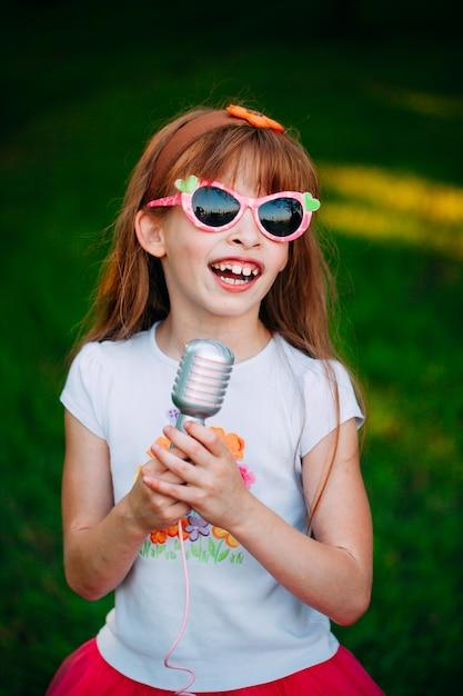 Petite fille chantant un karaoké Photo Premium